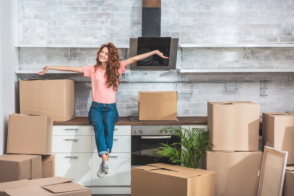 Smiling woman who has just moved in sits on boxes