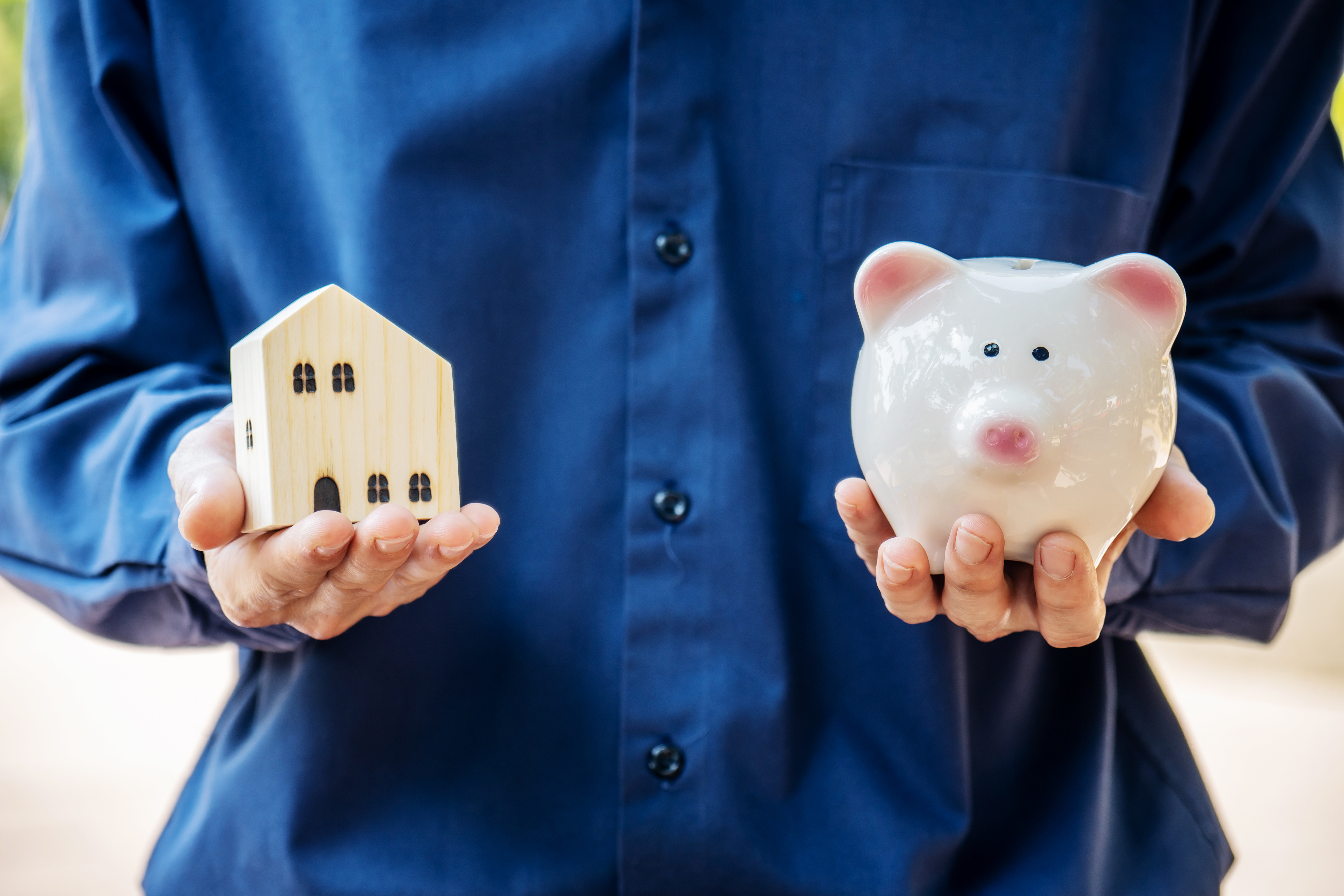 Man holding piggy ceramic bank and model home in hand